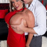 Mature pornstar Sally D'Angelo showing off great legs and unleashing huge boobs