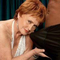 Red hair granny pornstar Valerie sucking off a massive black cock in white lingerie