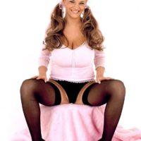 Blonde European pornstar Ines Cudna exposing huge boobs in black nylons and pigtails