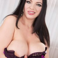 Brunette babe Joana Bliss freeing huge boobs from purple lingerie in mesh stockings