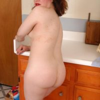 Mature redhead strips off sheer clothing and lingerie to pose naked in kitchen
