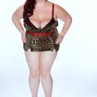 BBW solo model Trinety Guess showing off big tits after doffing spandex pants