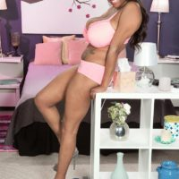 Black MILF Rachel Raxxx stripping down to matching pink bra and panty set on bed