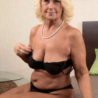 Blonde granny Regi letting saggy free from bra before oil massage from masseuse