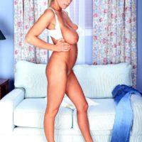 Blonde MILF pornstar Autumn Jade revealing huge tits while peeling off denim jeans