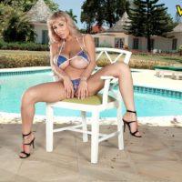 Blonde MILF pornstar Venera strutting solo in swimsuit and high heels by pool