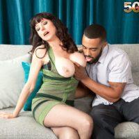 Brunette MILF over 50 Karen Kougar seducing younger man for sex on couch