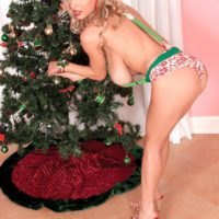 Busty blonde MILF Venera showing off great legs in high heels by Christmas tree