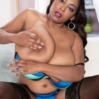 Ebony solo model Rachel Raxxx freeing massive juggs from bra in black stockings