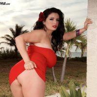 Brunette babe Arianna Sinn letting massive MILF tits loose outdoors on walkway