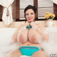 Brunette MILF Joana Bliss letting huge all natural boobs loose from bikini in bathtub
