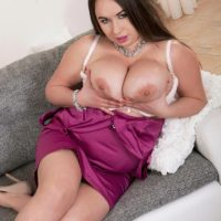 Brunette MILF Monica Love letting huge boobs loose from bra and dress in heels