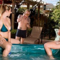 Busty MILF lesbians Brandy Talore and April McKenzie giving handjob in pool