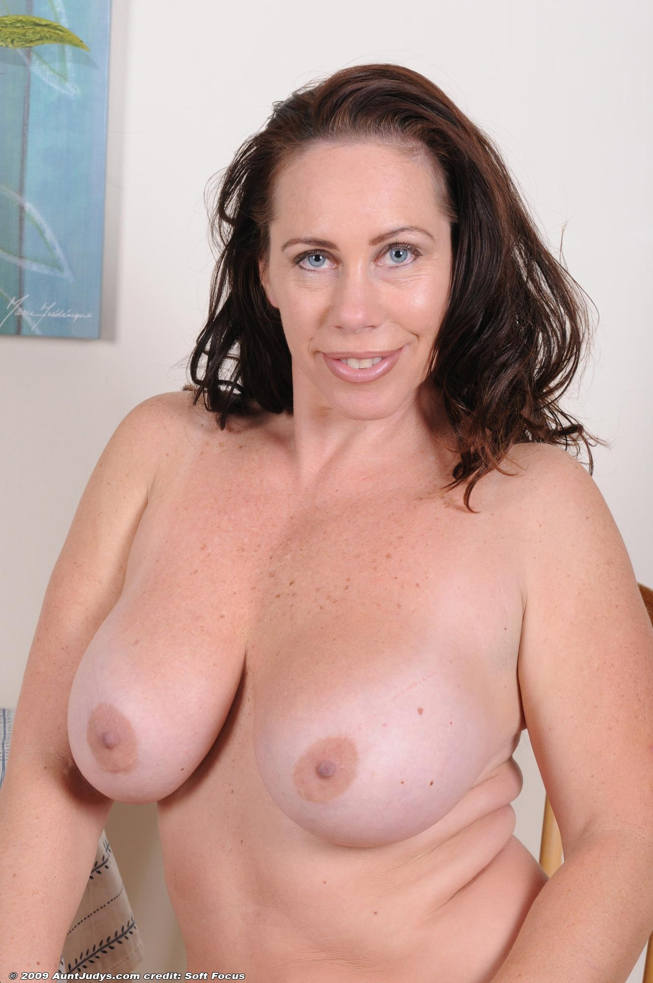 Experienced brunette woman exposing large all natural boobs and big butt