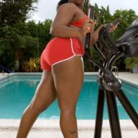 Fat black chick Keyona Kay oiling up sexy big butt outdoors by swimming pool