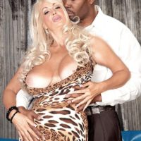 Leggy blonde MILF Brittany O'Neil releasing large tits for black man on leather sofa