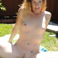 Older amateur woman strips off bikini to pose naked outdoors in back yard