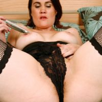 Older brunette lady in black stockings inserting sex toy into shaved vagina in heels