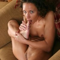 Older brunette woman with great legs sucking her own toes after undressing