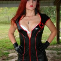 Redheaded Domme Amadahy modeling outdoors in latex outfit, boots and gloves