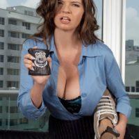 Big boobed brunette policewoman June Summers giving handjob to big cock