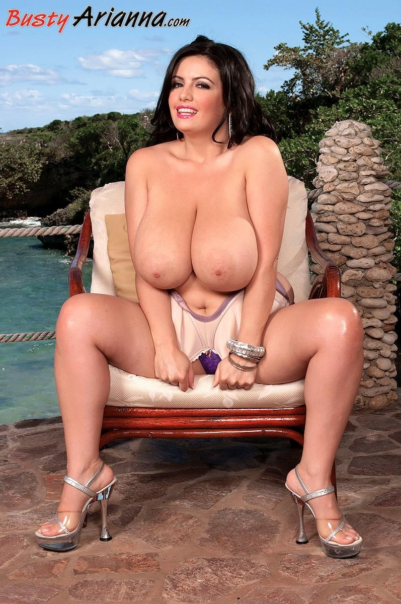 Busty brunette MILF Arianna Sinn pinching and licking her own nipples outdoors