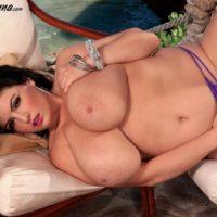 Busty brunette MILF Arianna Sinn pinching and licking her own nipples outdoors