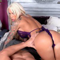 Tattooed blonde MILF pornstar Lolly Ink revealing round boobs for nipple sucking
