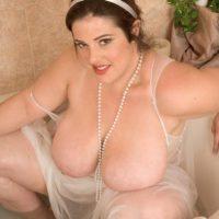 Tattooed brunette BBW Angel Sin releasing massive saggy tits from sheer lingerie