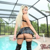 Blonde dominatrix Marsha May strutting topless by pool with riding crop in hand