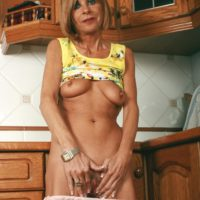 Middle aged housewife strips off jeans and underwear to model naked in kitchen
