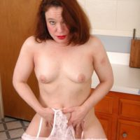 Older redhead wife stripping off sheer clothing and lingerie to pose nude in kitchen