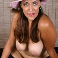 Busty mature woman in sun hat removes high heeled shoes from nylon clad feet