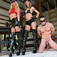 Two dommes in hats and long boots lead male slave by a leash