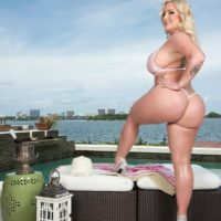 Blonde BBW Holly Wood struts about in a thong bikini next to the ocean
