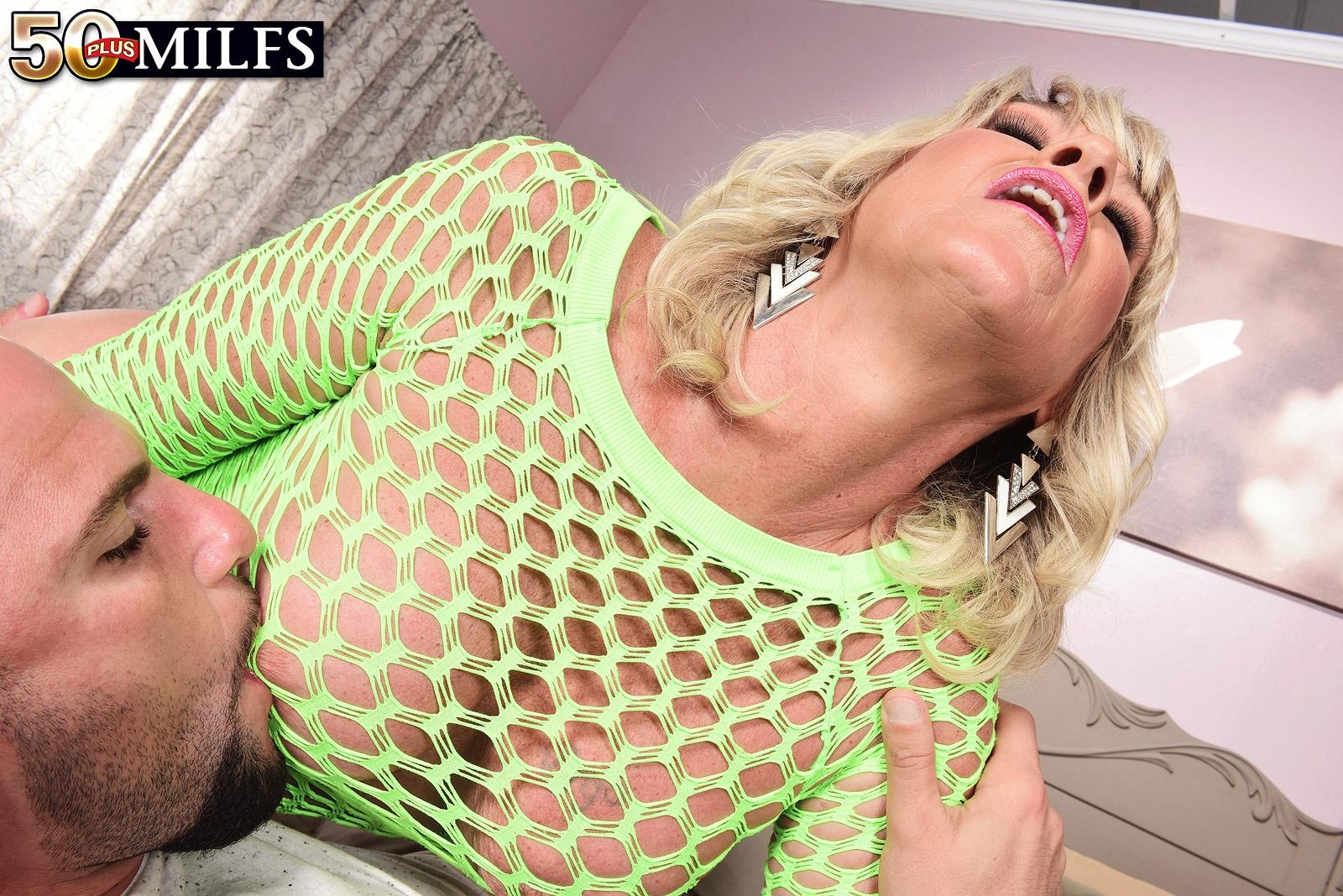 Blonde cougar Brandi Jaimes seduces a man in a see thru mesh dress and heels