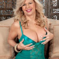 Mature blonde lady Miss Deb frees her huge tits from her lingerie on a sofa