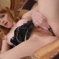Redhead solo girl with nice tits spreads the lips of her hairy pussy on her bed
