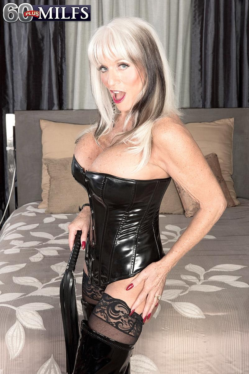 Big boobed 60 plus MILF Sally D'Angelo jerks a cock in latex boots and black corset