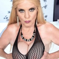 Blonde granny Charlie bares her big tits in over the knee boots and mesh bodystocking