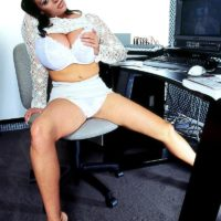 Brunette MILF Linsey Dawn McKenzie exposes her massive tits at her office desk