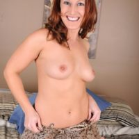 Middle aged redhead flaunts her tits and twat prior to toying her shaved pussy
