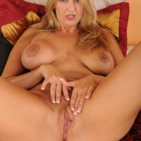 Older blonde MILF reveals her big tits prior to slipping off her thong and masturbating