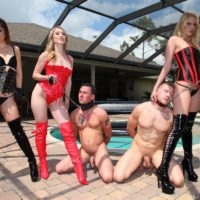 Three Dommes in fetish attire abuse two collared male subs on the pool patio