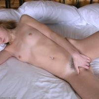 Amateur model pulls down her underwear prior to masturbating her hairy vagina