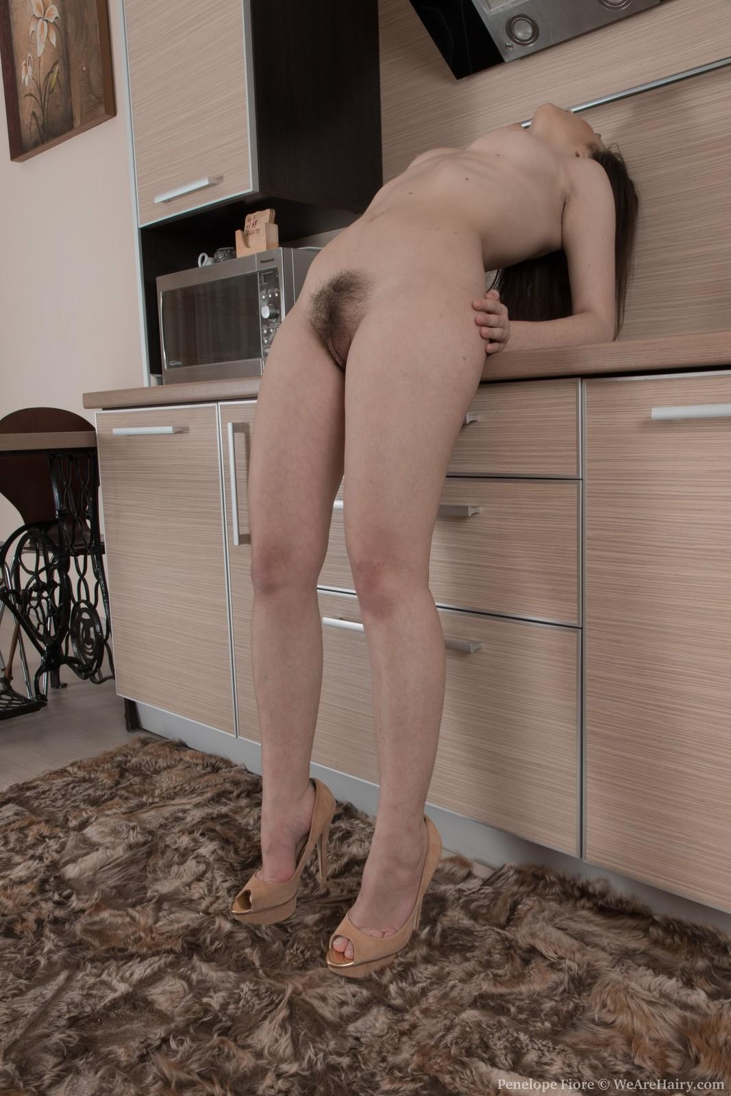 Amateur solo girl Penelope Fiore flaunts her hairy pussy in the kitchen