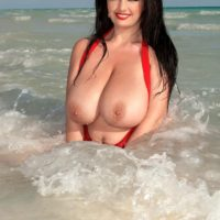 Dark haired BBW Arianna Sinn releases her massive tits from swimsuit at the beach