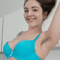 Hairy solo girl Cherry Bloom takes off her dress and lingerie to model in the nude