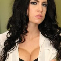 Hot brunette female Emmanuelle London removes her miniskirt to expose her bald cunt