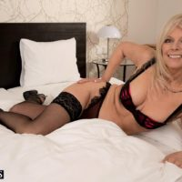 Mature blonde woman licks and sucks on a large dick in her black stockings